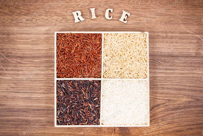 Heap of white, brown, red and black rice with inscription, healthy nutrition concept