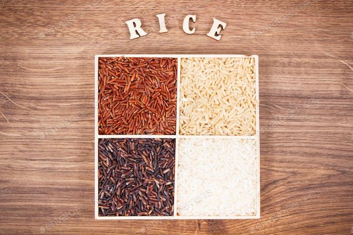 Haufen weißer, brauner, roter und schwarzer Reis mit Inschrift, gesundes Ernährungskonzept