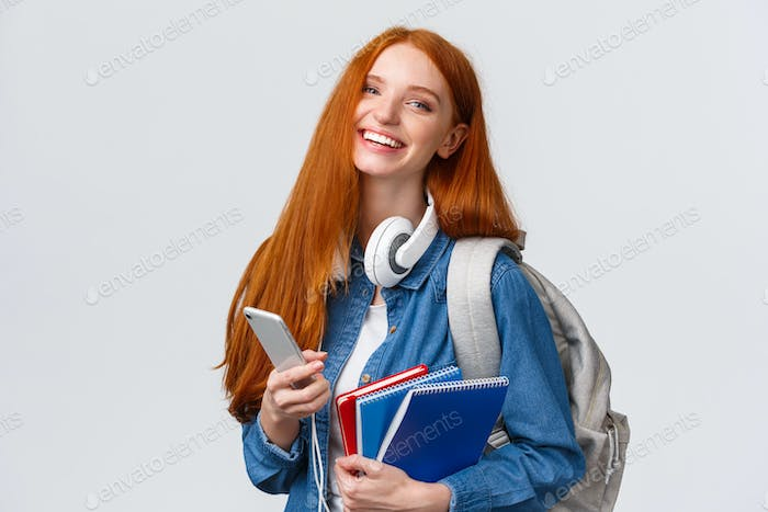 Cheerful, friendly and charismatic redhead woman laughing joyfully, texting friends, chatting with