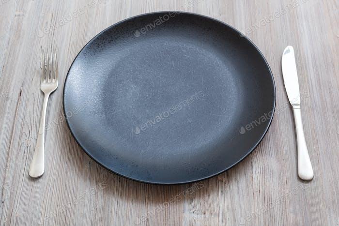 schwarzer Teller mit Messer, Löffel auf graubraunem Tisch
