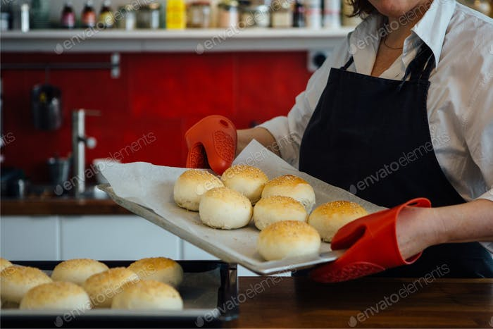 Baker holding oven tray with buns