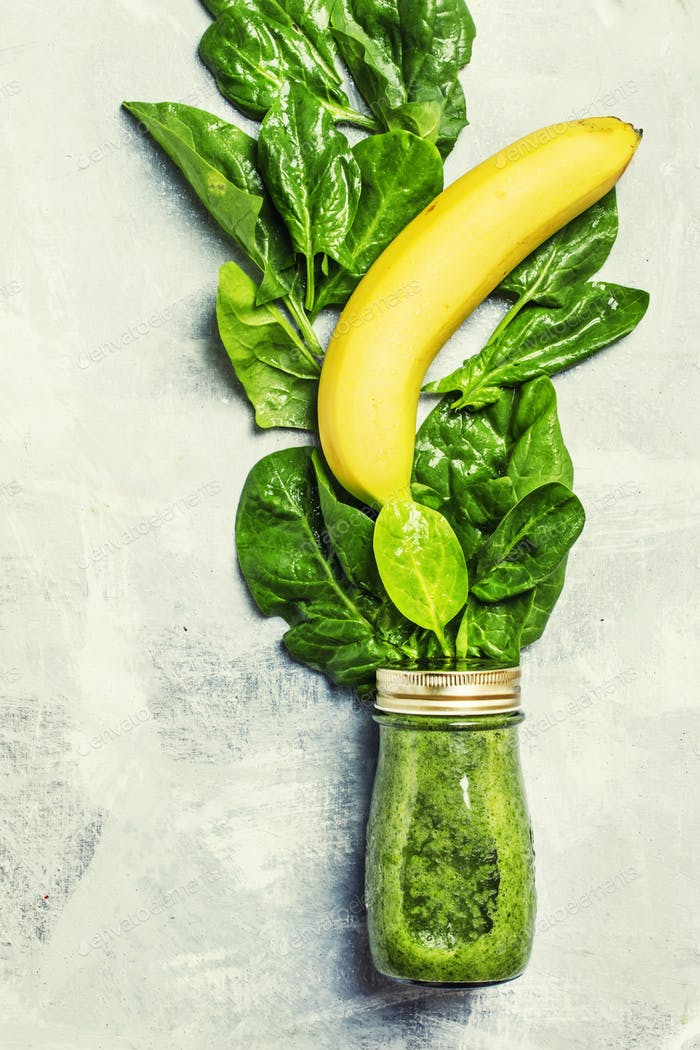 Green detox smoothies made from spinach leaves in a glass bottle