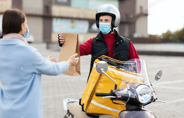 Courier On Motorbike Delivering Package Wearing Protective Mask Standing Outside
