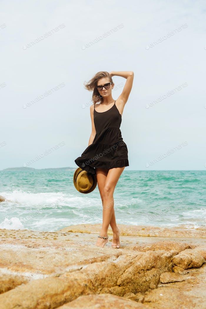 Cute girl in black summer dress at big stones.