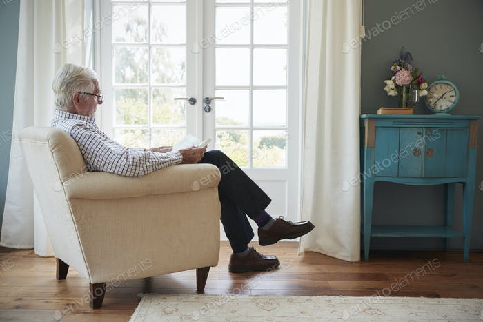 Senior man sitting in an armchair reading a book at home