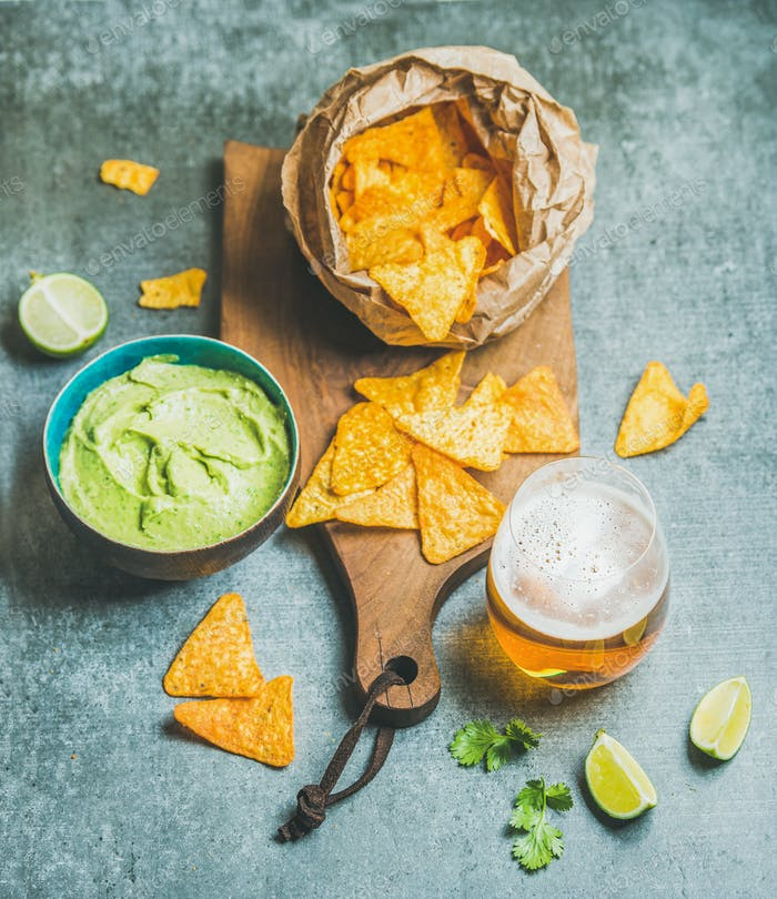 Mexican corn chips, fresh guacamole sauce and beer, concrete background