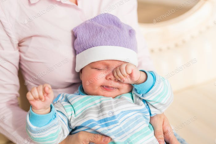 Portrait of newborn tired baby boy rubbing eyes