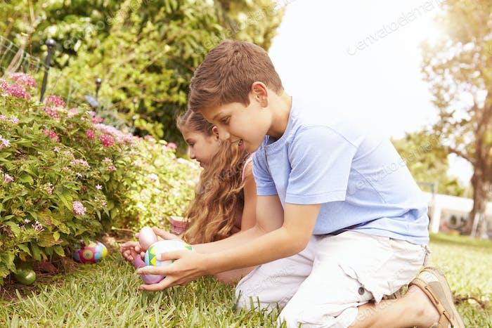Zwei Kinder mit Osterei Jagd In Garten