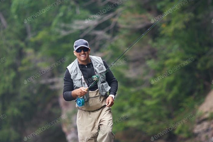 Cheerful man fishing in rough mountain river