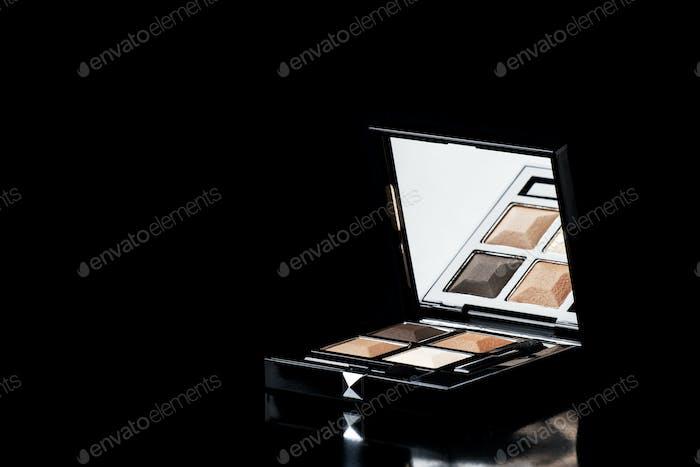 Brown sand eyeshadow in black box on glossy black background