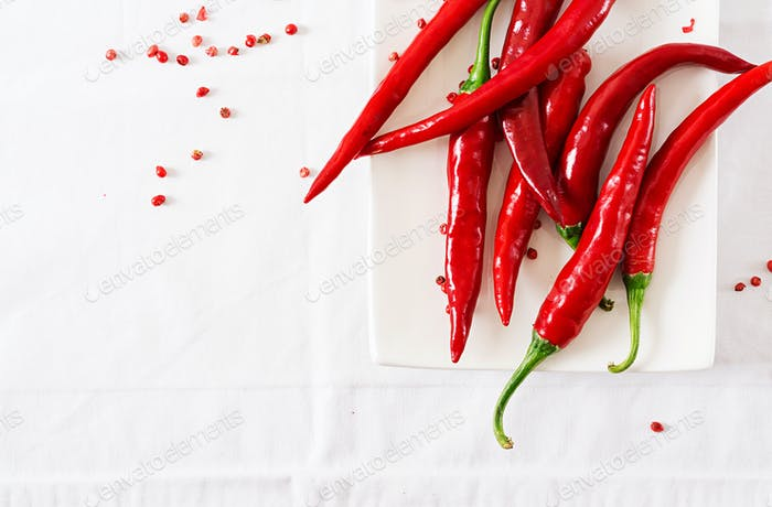 Red hot chili peppers in plate on white table. Top view. Flat lay