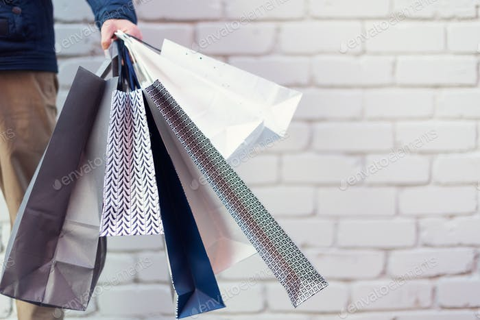 Male hand holding bunch of shopping bags with purchases near brick background. Copy space. Sale