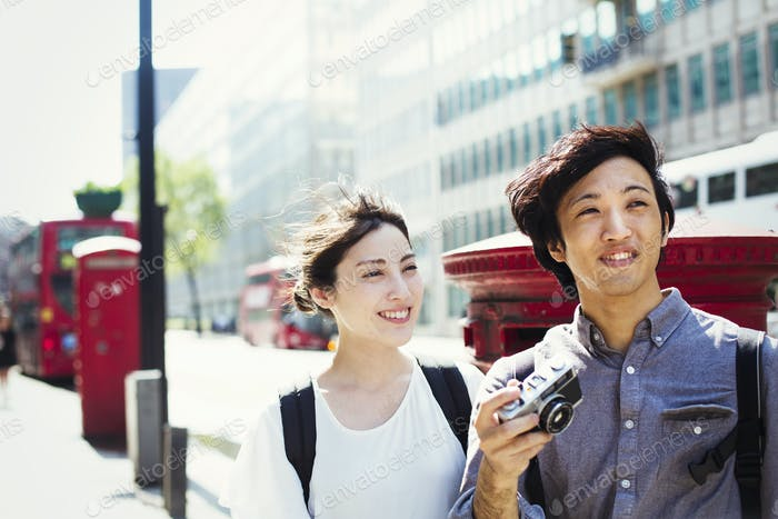 Young Japanese man and woman enjoying a day out in London, walking down a street.