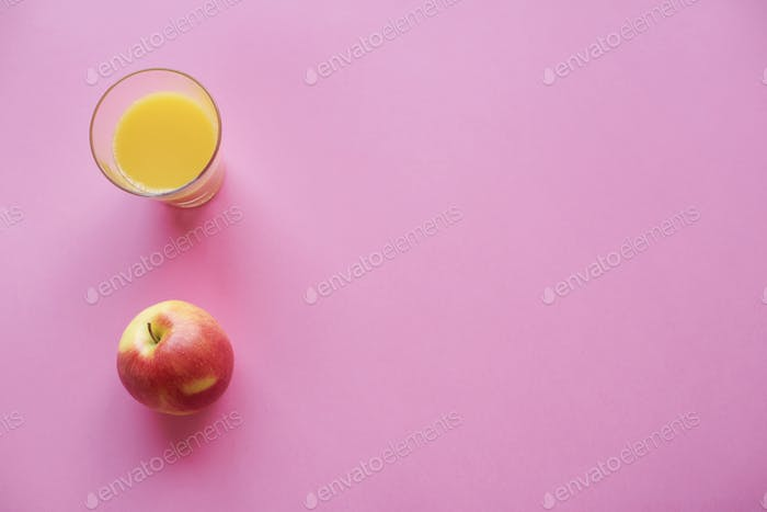 Main view of juice in drinking glass and apple