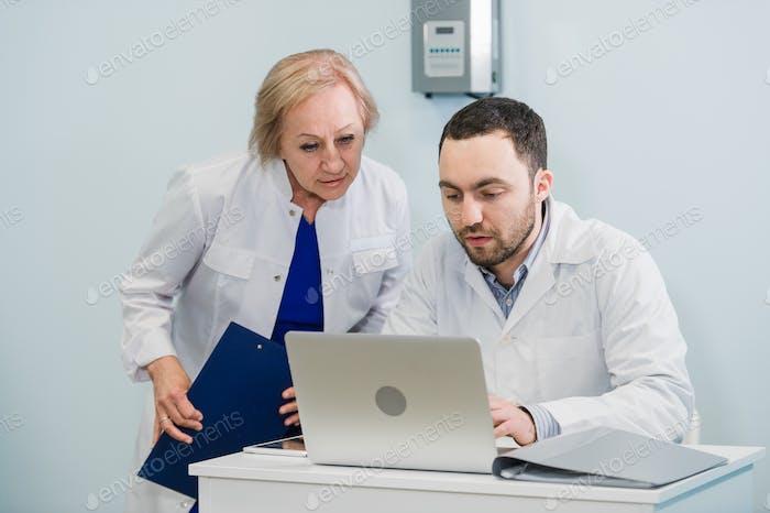 Arzt und Krankenschwester überprüfen Patienteninformationen auf einem Laptop in einer Büroeinrichtung