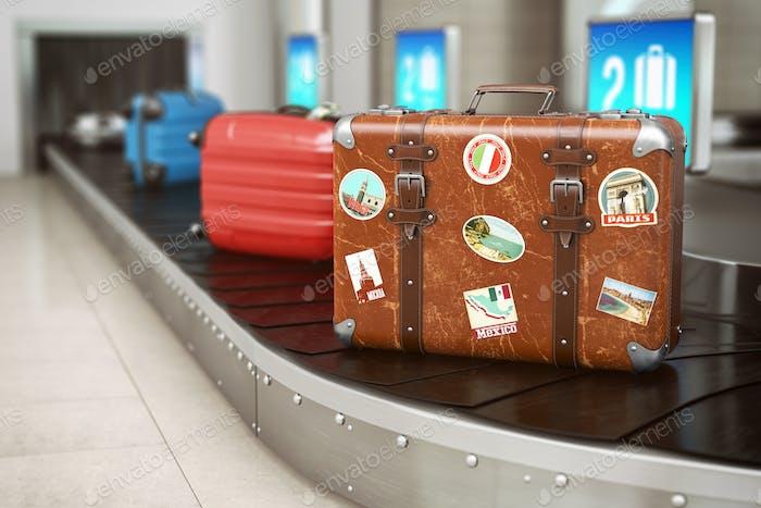 Alter Vintage-Koffer auf einem Flughafen-Gepäckförderband. Gepäck
