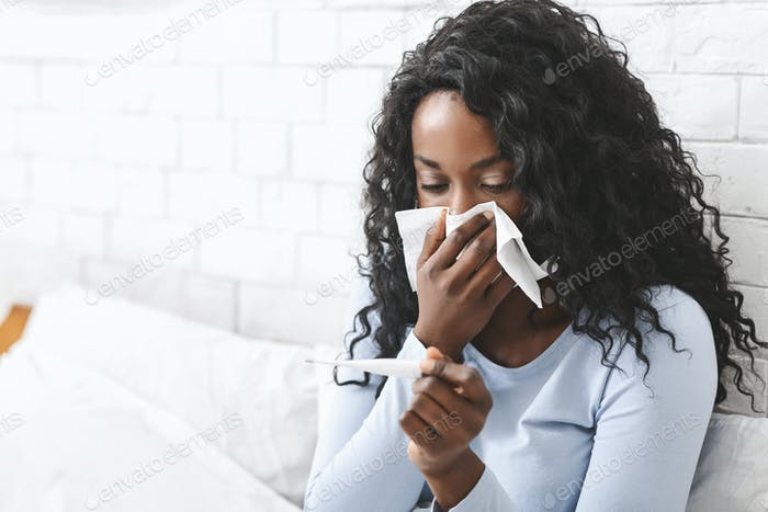 Sick young woman measuring body temperature in bed