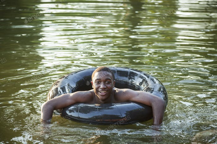 A boy floating in the water using a tyre swim float.