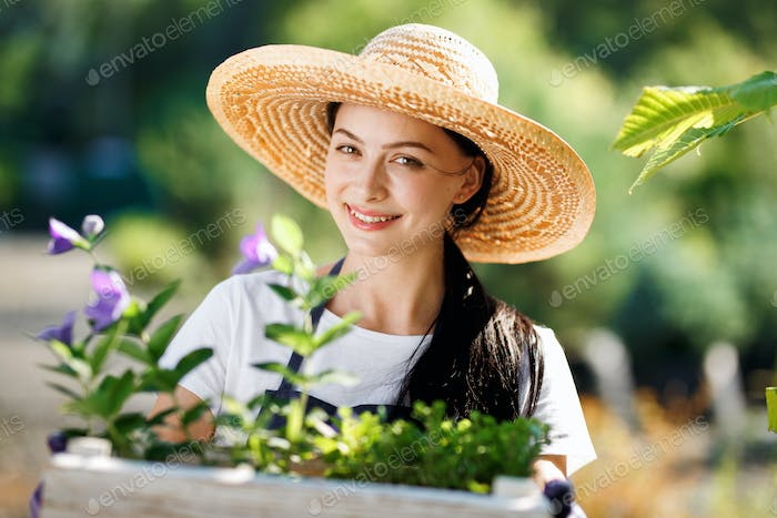 Portrait of cheerful young woman gardener with flowers in wooden box for sale in her shop