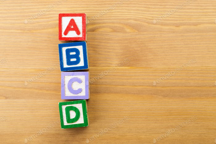 ABCD wooden toy block over the wooden background