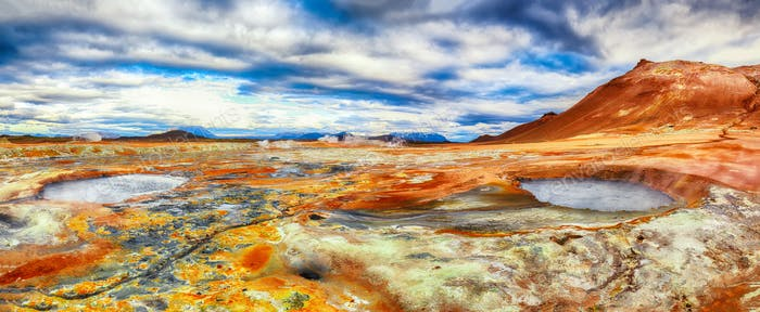 Boiling mudpots in the geothermal area Hverir and cracked ground around
