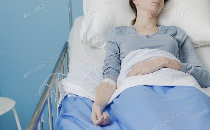 Patient in einem Krankenhausbett mit IV-Tropf