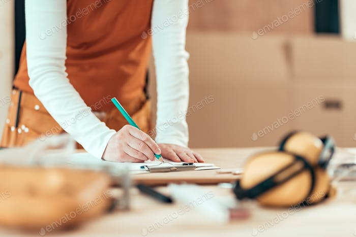 Female carpenter writing project notes in woodwork workshop