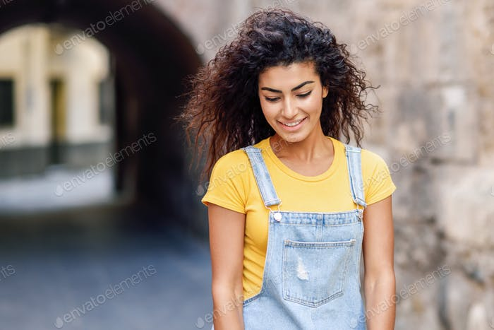 Young Arab woman with curly hairstyle outdoors.