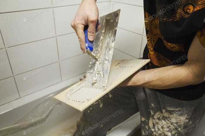 Close up of a builder, tiler spreading adhesive on the back a tile.