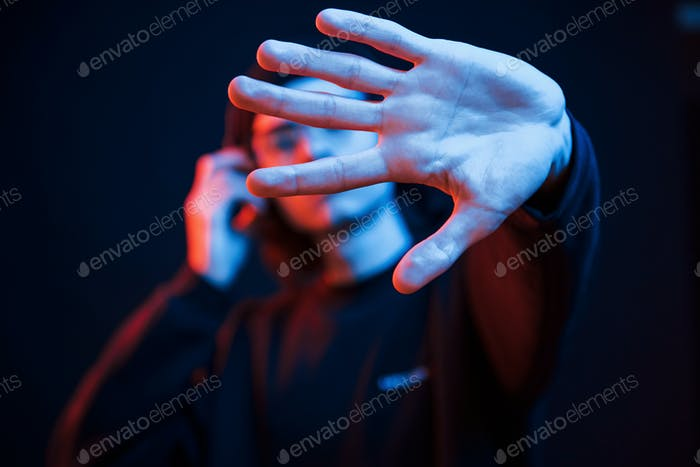 Focused photo. Studio shot in dark studio with neon light. Portrait of serious man