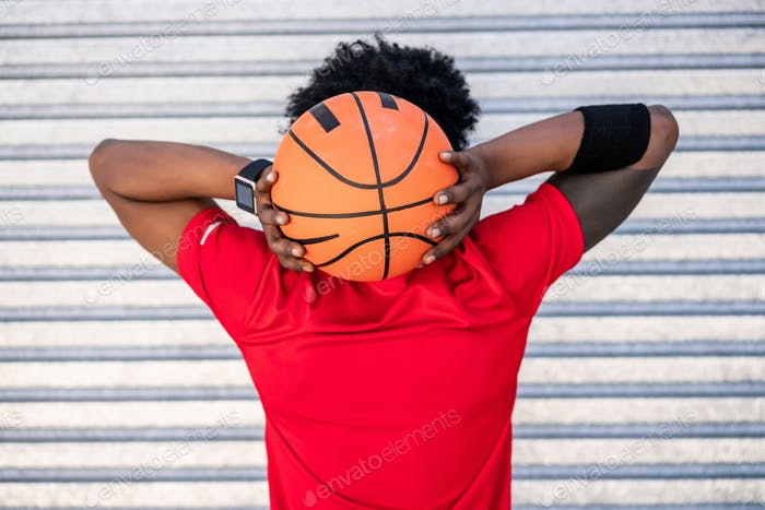 Afro athlete man holding a basketball ball outdoors.