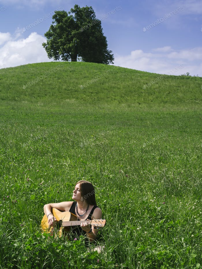 Woman playing guitar in large field