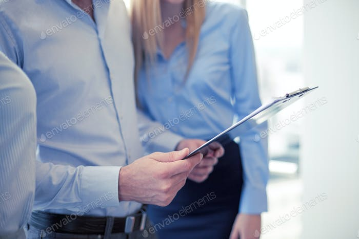 close up of business team looking at clipboard