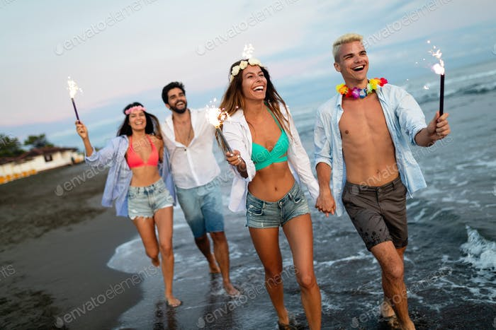 Happy group of friends lighting sparklers and enjoying freedom at beach during sunset