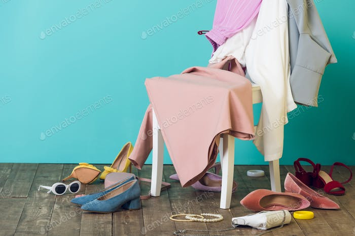 unordentliches Zimmer mit eleganter modischer Kleidung und Schuhen auf dem Stuhl
