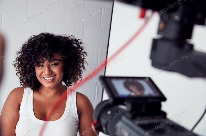 Female Model Posing For Video Camera On Film Set