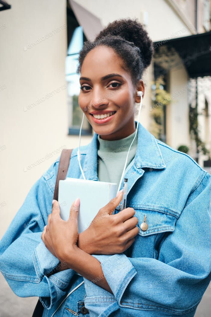 African American student girl in denim jacket joyfully looking in camera on city street