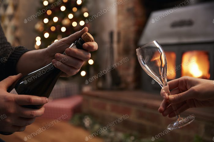 Couple Opening Champagne In Room Decorated For Christmas