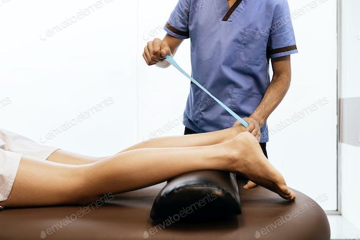 Physiotherapeut, die einer Frau eine Kalbtherapie geben