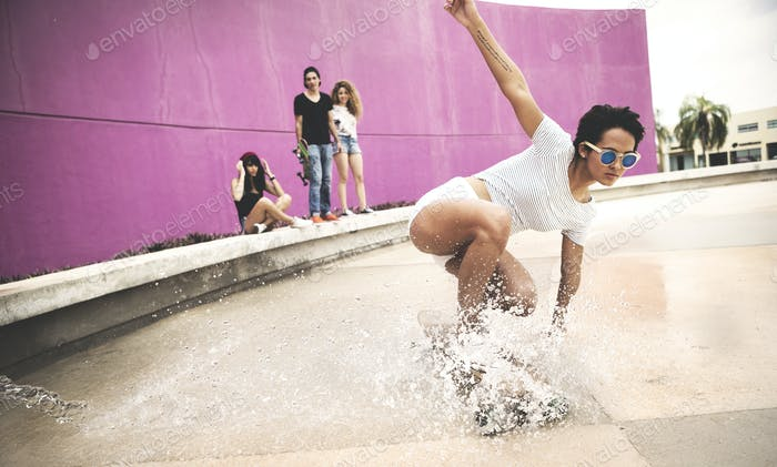 A young woman crouching down on a skateboard to create a water spray.