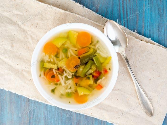 Helle Frühlingsgemüse vegetarische Suppe, Leinenserviette, Draufsicht, blauer Hintergrund.