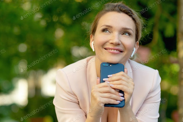 Close-up portrait of a smiling woman with smartphone on the street.