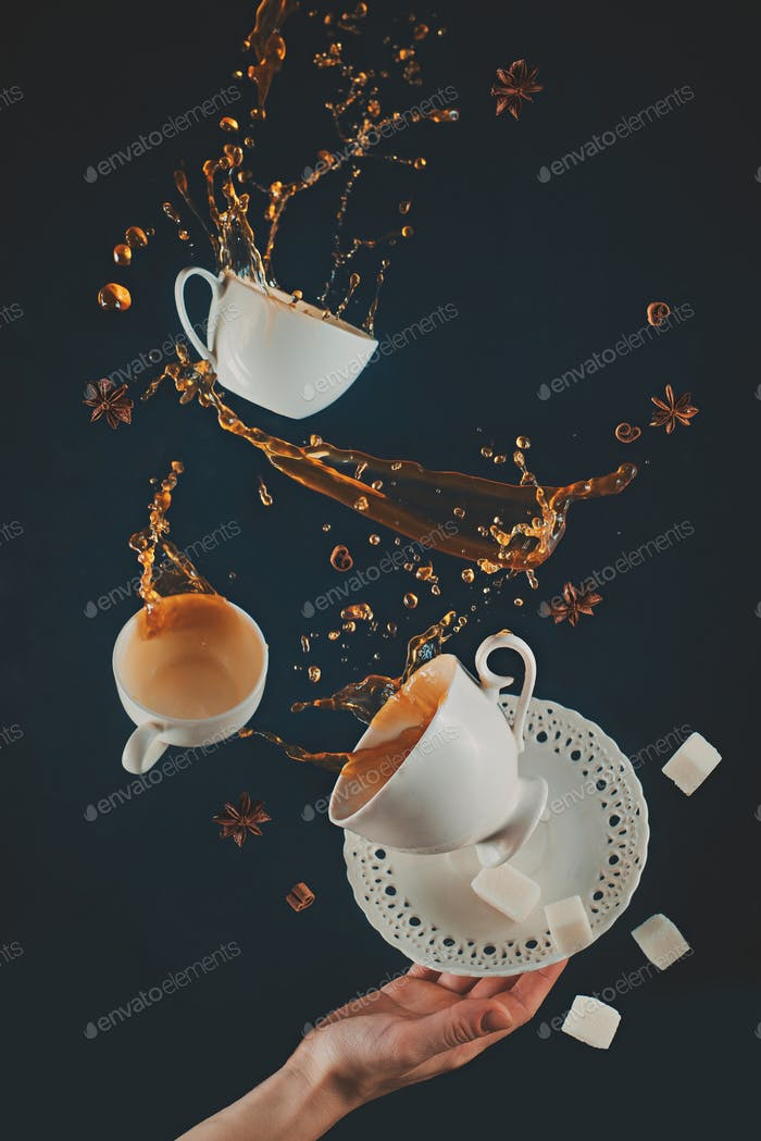 Flying coffee cups with saucer, dynamic splashes and falling sugar cubes on a black background