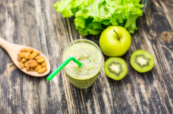 Healthy green smoothie with kiwi, apple on rustic wood background.