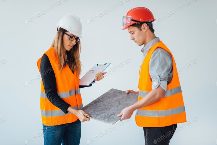 Architects examining tiles on construction site