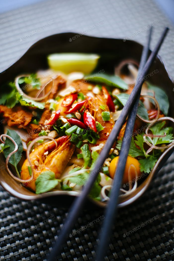 High angle close up of chopsticks on bowl with Asian food containing noodles, prawns, vegetables and