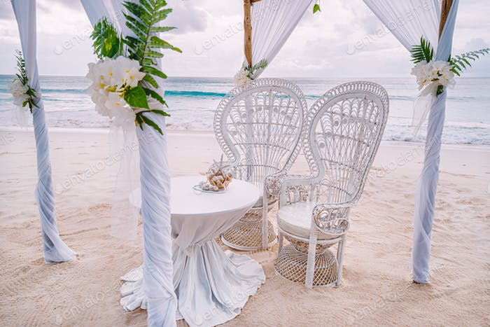 Decorated romantic wedding setting with table and chairs on sandy tropical beach with ocean and