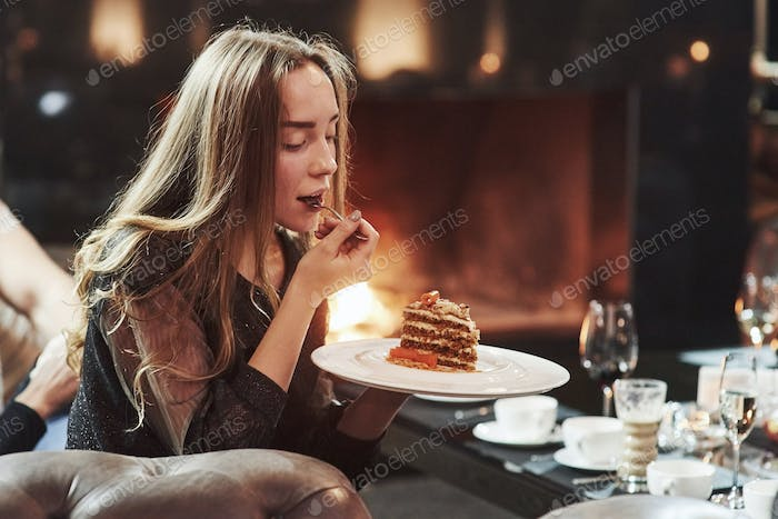 Time for a dessert. Cute girl trying fresh cake while sits in the room with beautiful fireplace