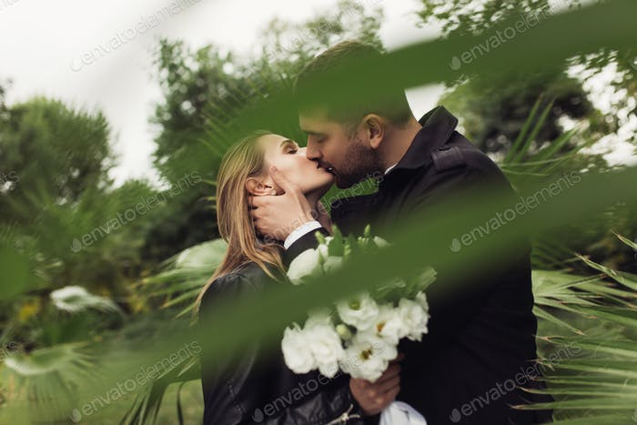 Young handsome man in trench coat dreamily kissing pretty woman