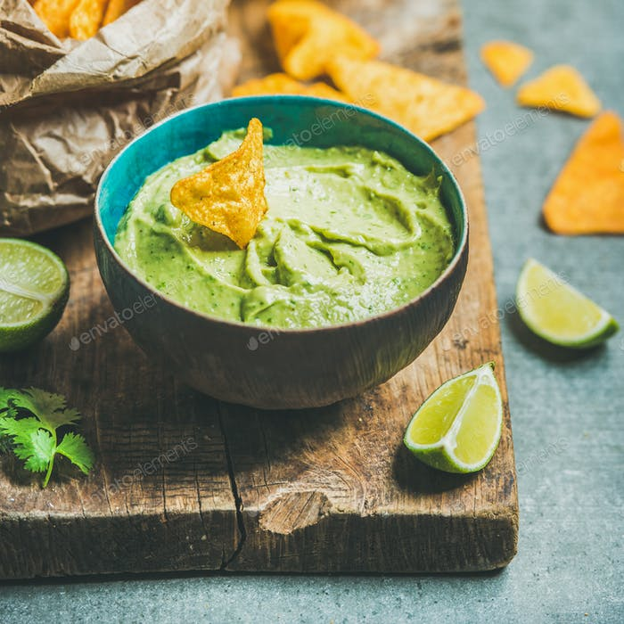 Fresh guacamole sauce in blue bowl and chips, square crop